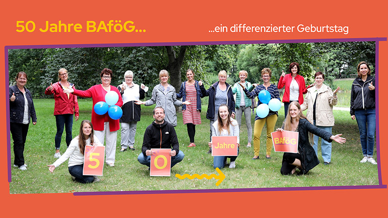 """Gruppenfoto von Mitarbeitenden des BAföG-Amts, einige halten Ballons und Schilder mit der Aufschrift """"50 Jahre BAföG"""" in den Händen"""