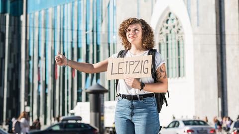"""Junge Frau hält Schild mit Aufschrift """"Leipzig"""" in der Hand"""
