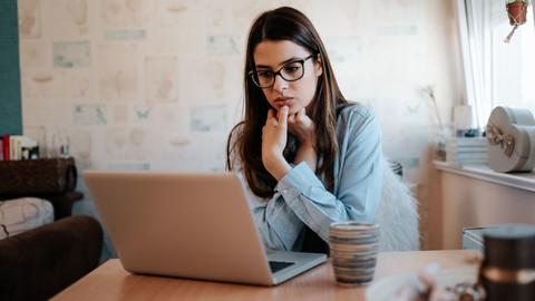 Eine Studentin sitzt vor ihrem Laptop und sieht ängstlich aus